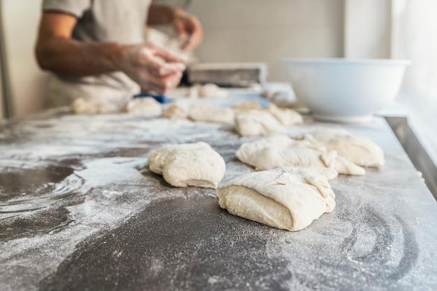 Mano dell'uomo del panettiere che sparge farina all'impasto. concetto di panetteria.