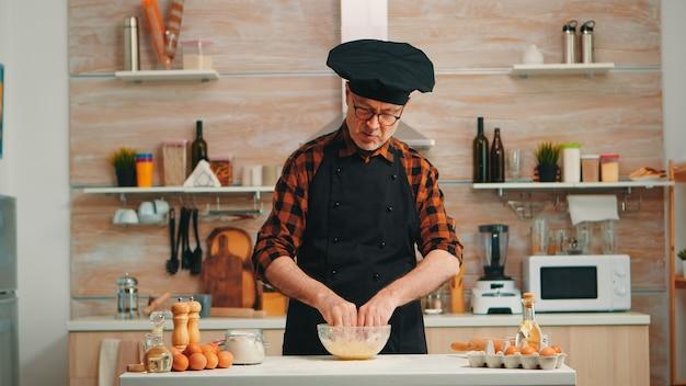 Uomo del panettiere che usa la farina per una gustosa ricetta tradizionale nella cucina di casa che parla alla macchina fotografica. influenzatore chef blogger in pensione che utilizza la tecnologia internet per comunicare sui social media con apparecchiature digitali
