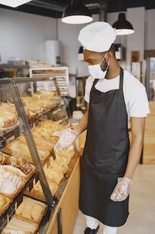 Baker in uniforme dando consigli sulla pasticceria. uomo che indossa una maschera protettiva. comprare pane fresco.
