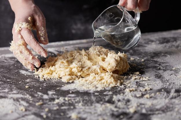La donna del panettiere che aggiunge acqua impasta la pasta per la cottura