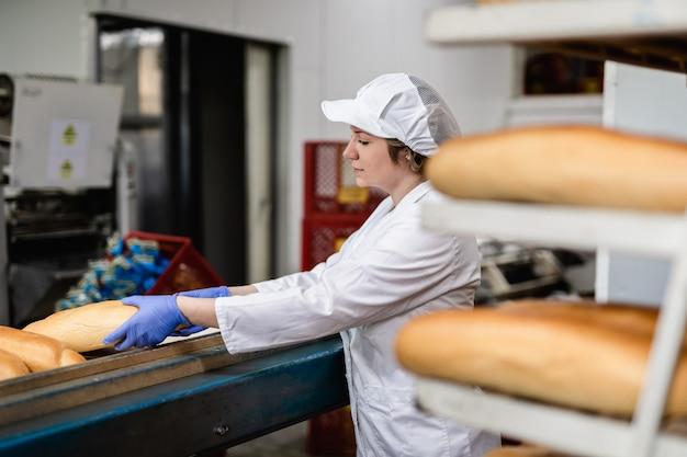 Donna del panettiere che lavora alla linea di produzione del pane.
