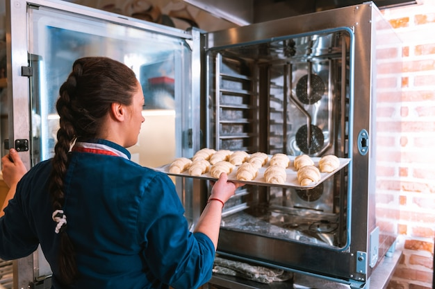 Baker lavorando. fornaio esperto professionista con treccia a lisca di pesce che mette nel forno la teglia con i croissant