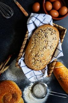 Concetto di panetteria. un assortimento di diversi tipi di pane su uno sfondo scuro. pane in un cestino, uova, farina, spighe di grano vista dall'alto (piatto). spazio per il testo. vertcal