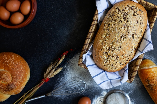 Concetto di panetteria. un assortimento di diversi tipi di pane su uno sfondo scuro. pane in un cestino, uova, farina, spighe di grano vista dall'alto (piatto). spazio per il testo