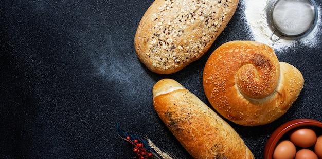 Concetto di panetteria. un assortimento di diversi tipi di pane su uno sfondo scuro. uova, farina, spighe di grano. vista dall'alto (piatto). spazio per il testo