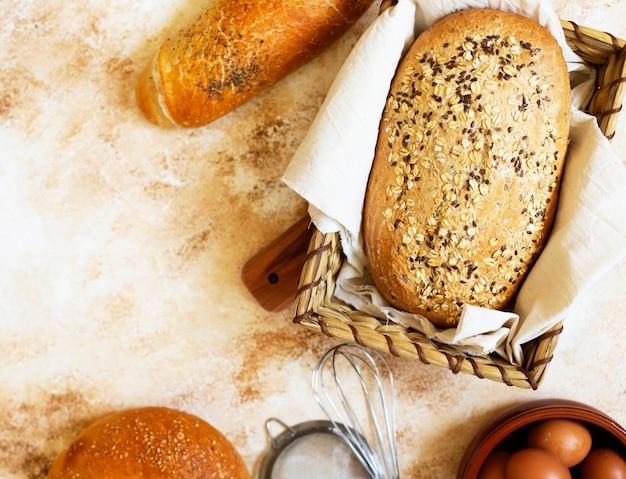 Concetto di panetteria. un assortimento di diversi tipi di pane su uno sfondo chiaro. vista dall'alto (piatto). spazio per il testo