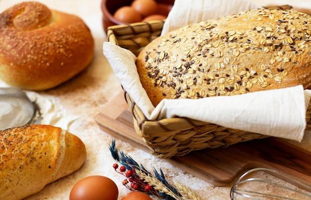 Concetto di panetteria. un assortimento di diversi tipi di pane su uno sfondo di marmo chiaro. uova, farina, spighe di grano. avvicinamento