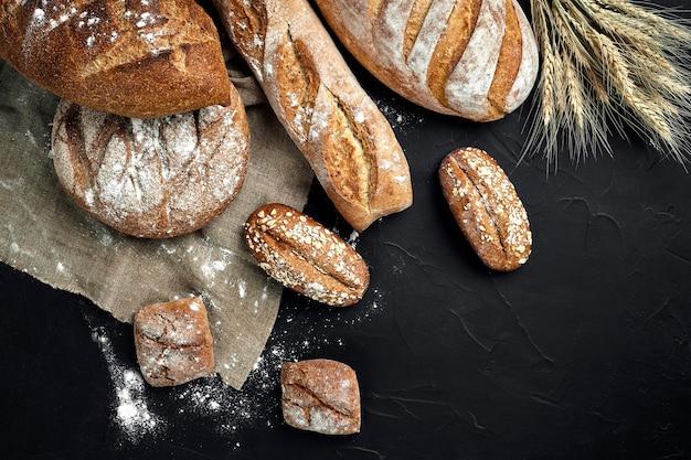 Pagnotte e panini croccanti rustici dell'oro della panetteria sul fondo nero della lavagna