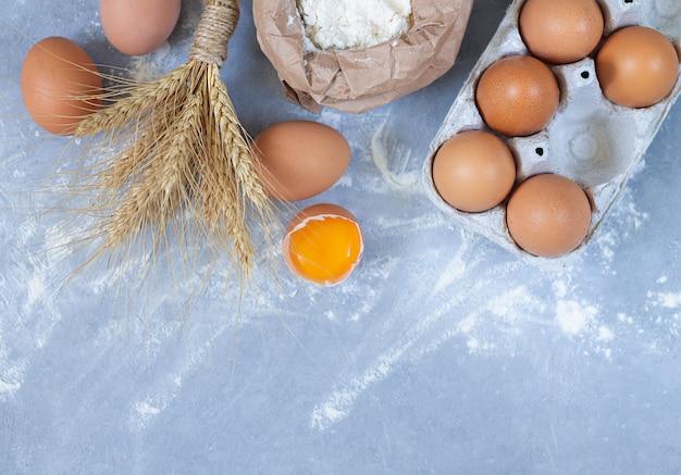 Ingredienti del forno: uova, spighe di grano e sacco di carta di farina sulla vista di pietra del piano d'appoggio