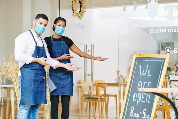 Lavoratori di panetteria che invitano i clienti