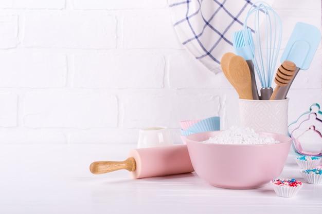 Utensili da forno. utensili da cucina per la cottura su un fondo di legno bianco.