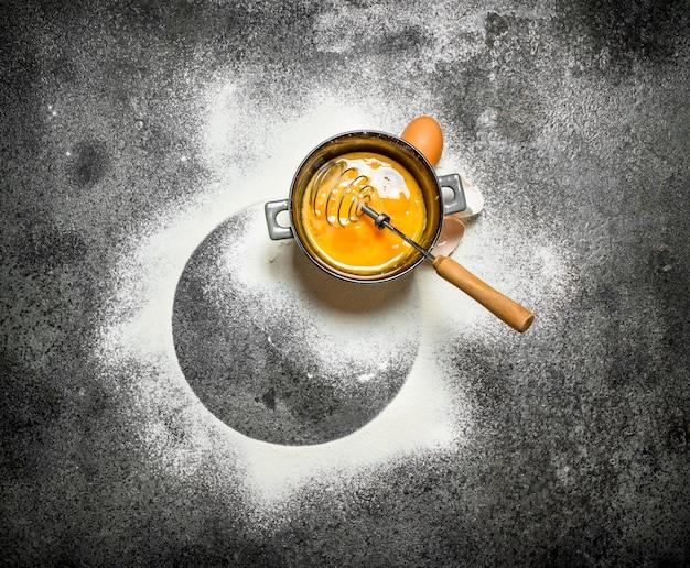 Sfondo di cottura. sbattere le uova con la farina setacciata sul tavolo rustico.