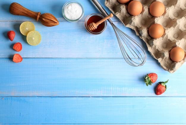 Sfondo di cottura con ingredienti di cottura come uova, fragole, limone, zucchero dus e miele. adatto per sfondo o carta da parati su sfondo blu in legno