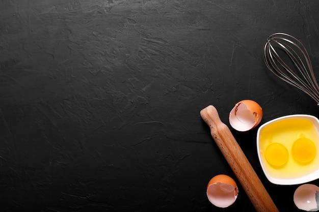 Sfondo di cottura con guscio d'uovo e mattarello. copia spazio.