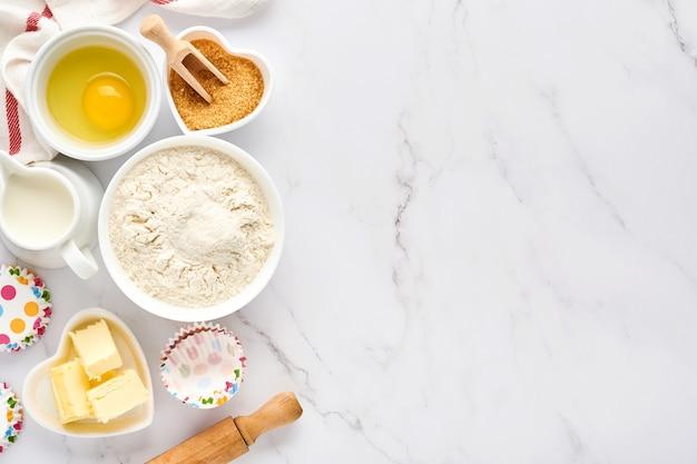Sfondo di cottura con farina, uova, utensili da cucina, utensili e stampi per biscotti sul tavolo bianco