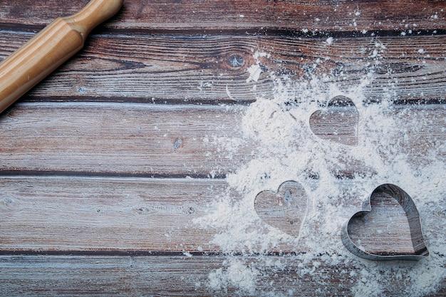Sfondo di cottura con farina e forma di cuore sul tavolo da cucina scuro con spazio per il testo.