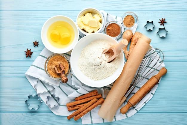 Sfondo di cottura con ingredienti per fare la farina di pan di zenzero, uova, utensili da cucina, utensili e stampi per biscotti sul tavolo di legno blu. vista dall'alto. stile piatto. modello. cottura di natale.