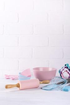 Sfondo di cottura con utensili da cucina: mattarello, cucchiai di legno, frusta, setaccio, bakeware e formina per biscotti su fondo di legno bianco.