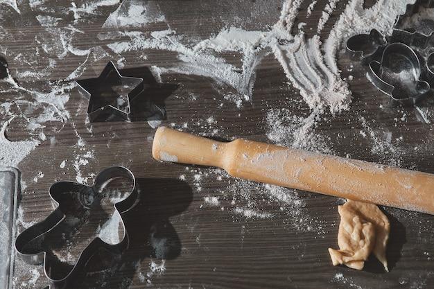 Biscotti di natale di cottura sulla tavola di legno marrone scuro. famiglia che fa l'uomo di pan di zenzero, tagliando i biscotti di pasta di pan di zenzero, vista dall'alto