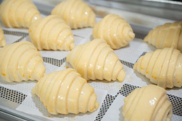 Cuocere i croissant classici a casa e spennellare l'uovo sui croissant crudi.