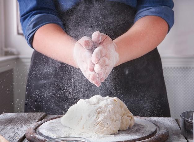 Concetto di cottura. farina, latte e uova sul tagliere di legno, ingredienti per pasticceria. immagine ritagliata di donna irriconoscibile impastare e cospargere di pasta per pizza lievitata. primo piano femminile del panettiere, verticale