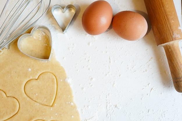 Concetto di cottura per san valentino con frese a forma di cuore e uova sulla tavola di legno bianca con copyspace