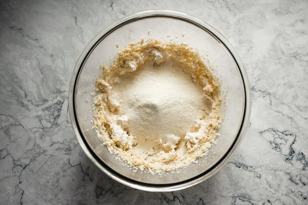 Fare biscotti. farina, lievito e sale aggiunti all'impasto in una grande ciotola di vetro. foto orizzontale vista dall'alto.