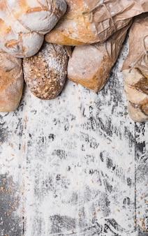Sfondo di concetto di cottura e cottura. bordo di diversi tipi di pane, avvolto nella vista superiore della carta del mestiere con lo spazio della copia sulla tavola di legno, cosparsa di farina, verticale