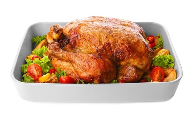 Teglia da forno con tacchino arrosto e verdure su sfondo bianco