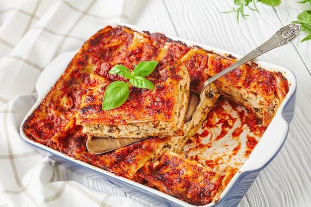 Piatto da forno con lasagne vegetariane di tofu, funghi, salsa di passata con foglie di basilico fresco su una superficie di legno bianco, primo piano