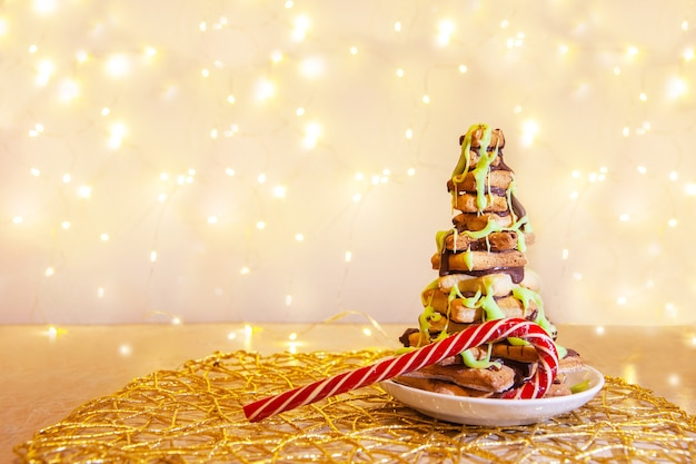 Cuocere sotto forma di albero di natale con caramello di natale sullo sfondo di una ghirlanda luminosa