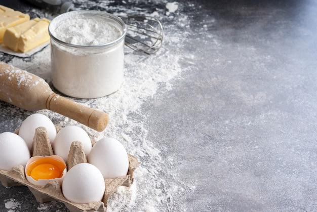 Ingredienti per la cottura: farina, uova, burro e zucchero, con il mattarello su un tavolo
