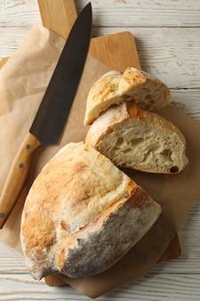 Carta da forno con pane e coltello su fondo di legno bianco