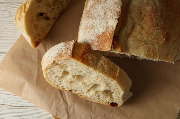 Carta da forno con pane su fondo di legno bianco