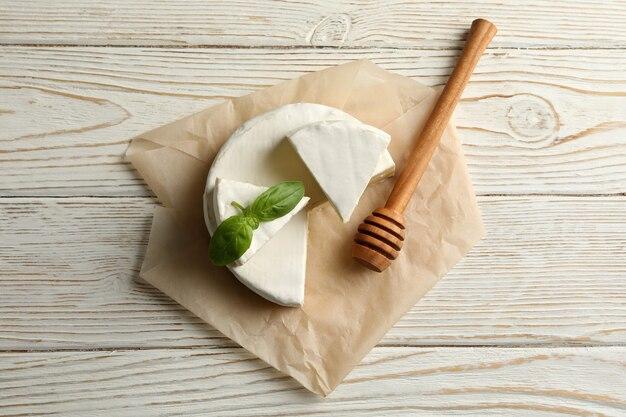 Carta da forno con formaggio camembert, basilico e mestolo su fondo in legno