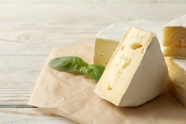 Carta da forno con formaggio camembert e basilico su fondo in legno