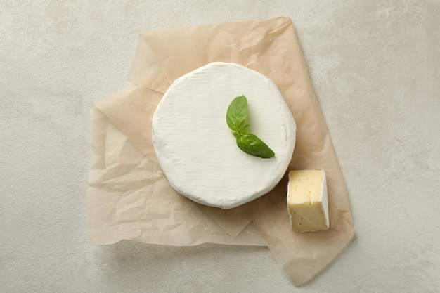 Carta da forno con formaggio camembert su sfondo bianco con texture