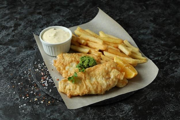 Carta da forno con pesce fritto e patatine fritte sul tavolo smokey nero