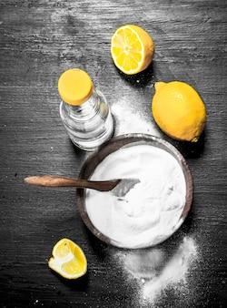 Bicarbonato di sodio in una ciotola con aceto e fette di limone.