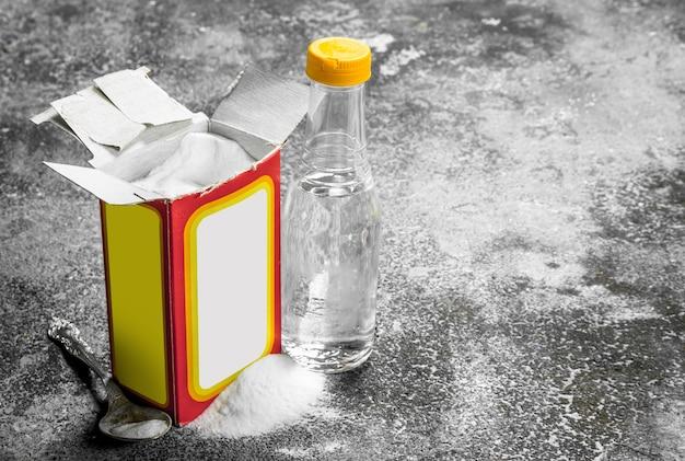 Bicarbonato di sodio con aceto. su fondo rustico.