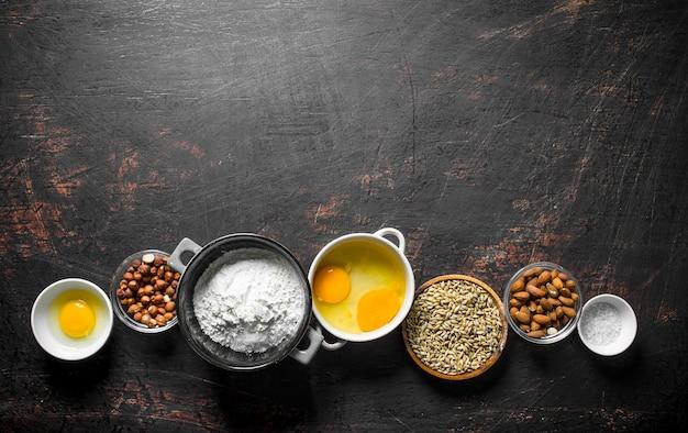 Superficie di cottura. vari ingredienti per l'impasto in ciotole. su superficie rustica scura