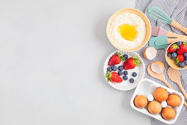 Utensili da forno e ingredienti da cucina per torte, biscotti, pasta e pasticceria. lay piatto con uova, farina, frutti di bosco.
