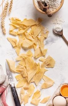 Parete di cottura con maltagliati di pasta fatta in casa cotta e fresca. cucina italiana tradizionale. concetto di cucina. vista dall'alto.
