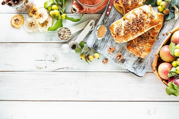 Cottura con mela, mela appena sfornata e panini alla cannella a base di pasta sfoglia su un tavolo di legno bianco. vista dall'alto, stile rustico, copia spazio.