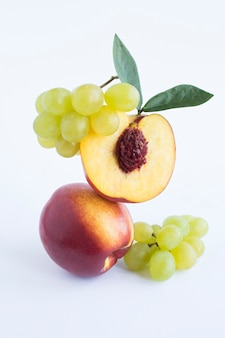 Equilibrio di nettarine e uva verde su fondo bianco. avvicinamento. posizione verticale.