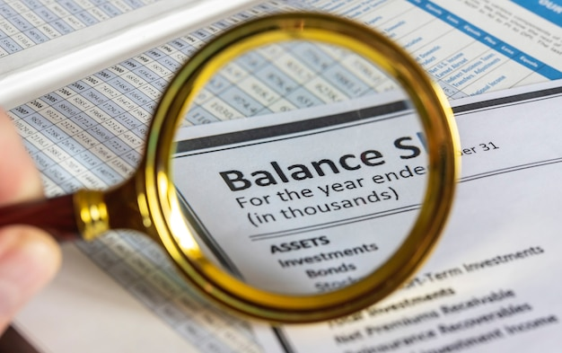 Parola di bilancio attraverso una lente di ingrandimento sullo sfondo di un documento e una tabella di cifre
