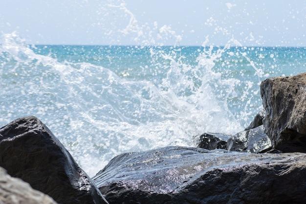 Bilancia la piramide di pietre zen sulla spiaggia di ciottoli con un'onda che spruzza.