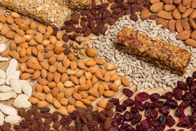 Barretta di muesli proteica bilanciata. frutta a guscio, semi, cereali, spighette di grano. alimento vegetariano di dieta sana. vista dall'alto. superficie in legno. avvicinamento