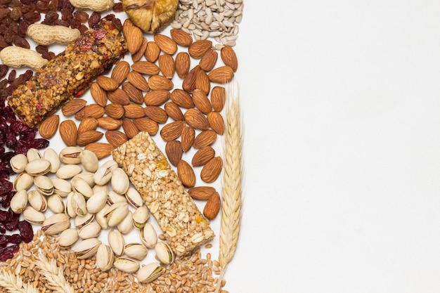Barretta di muesli proteica bilanciata. frutta a guscio, semi, cereali su fondo in legno.