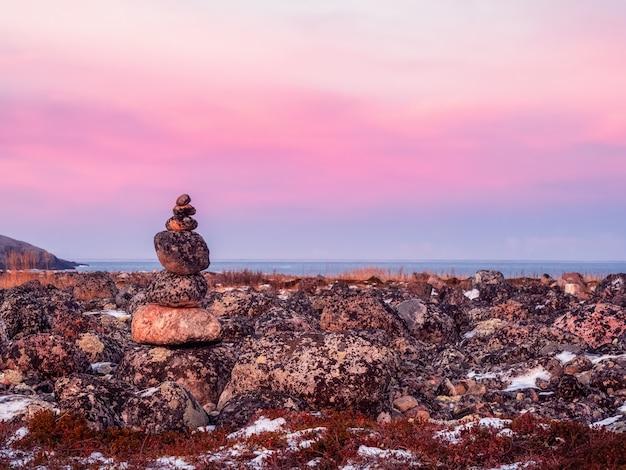 Pila equilibrata di pietre nella tundra invernale. la regione della teriberka. russia.